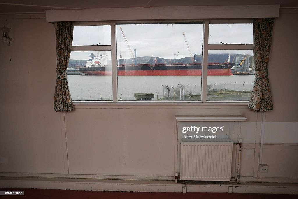 A modern cargo ship is seen through the Captain's Quarters onboard HMS Caroline on January 29, 2013 in Belfast, Northern Ireland. A National Heritage Memorial Fund grant of 1.097 m GBP will go towards urgent preventative work to secure the Caroline. An application for more funding is being made in order to proceed with full restoration of the 446 ft ship. Built by Cammell Laird at Birkenhead in 1914 she was part of the 4th Light Cruiser Squadron which saw action in the Battle of Jutland in 1916 and is the last surviving Royal Navy ship from that period still afloat. At the time of her decommissioning in 2011, she was the second oldest ship still in Royal Navy service, HMS Victory Nelson's flagship preserved at Portsmouth, being the oldest. Caroline was converted into a depot and training ship for The Royal Navy Reserve in Alexandra Dock in Belfast in later years.