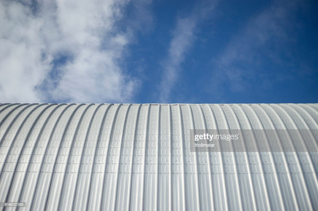 Modern curved roof with blue sky and clouds : Stock Photo