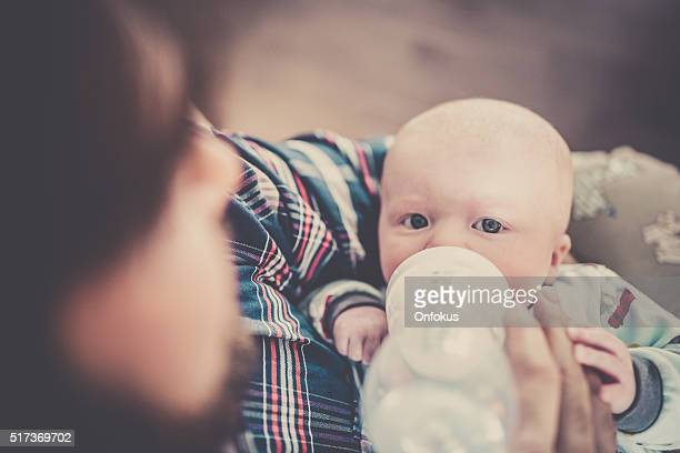 Modern Dad Feeding his Baby Boy with Bottle