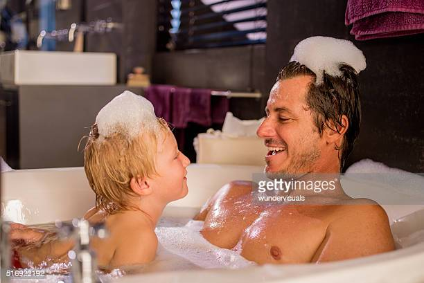 Moderne Vater spielt mit seinem Sohn in Schaumbad wie zu Hause fühlen.