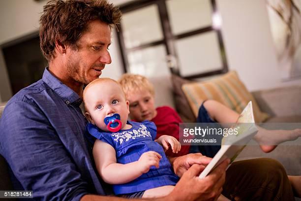 Moderne Vater lesen ein Buch für seine Kinder auf Sofa