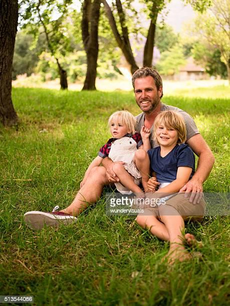Moderno padre seduto al parco con i suoi due bambini.