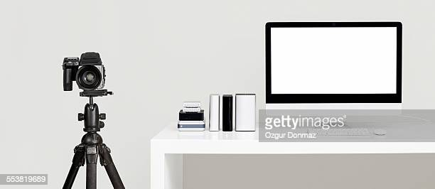 Modern desk with computer, camera and hard drives