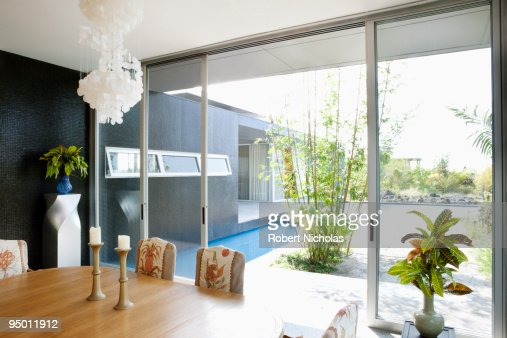 Modern Dining Room Overlooking Swimming Pool Stock Photo