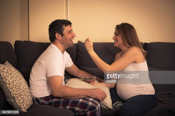 Modern Eastern European couple at home, pregnant woman and her husband spending time together