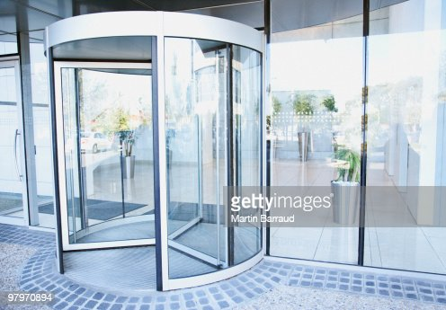 Modern entrance with revolving door : Stock Photo
