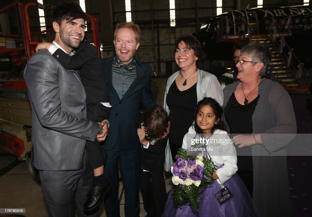 Modern Family actor Jesse Tyler Ferguson and his husband Justin Mikita (L) poses with the newly wed couple Lynley Bendall and Ally Wanikau (R) and their children after arriving at the Air New Zealand hanger on August 19, 2013 in Auckland, New Zealand.