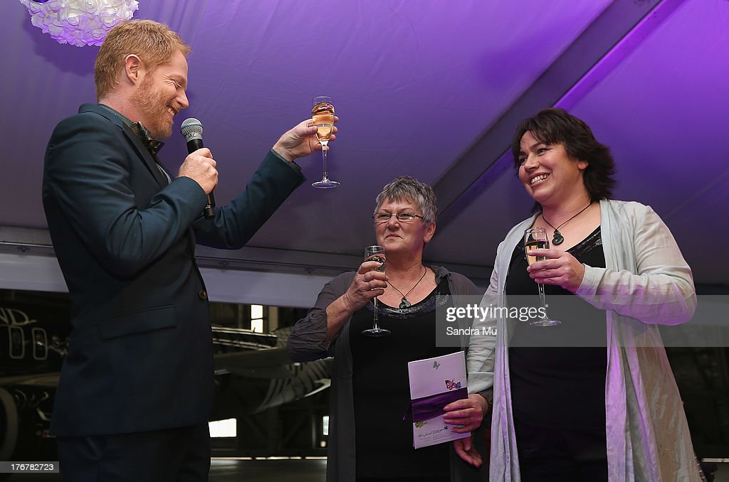 Modern Family actor Jesse Tyler Ferguson (L) toasts the newly wed couple Ally Wanikau and Lynley Bendall during the reception inside the Air New Zealand hanger on August 19, 2013 in Auckland, New Zealand.