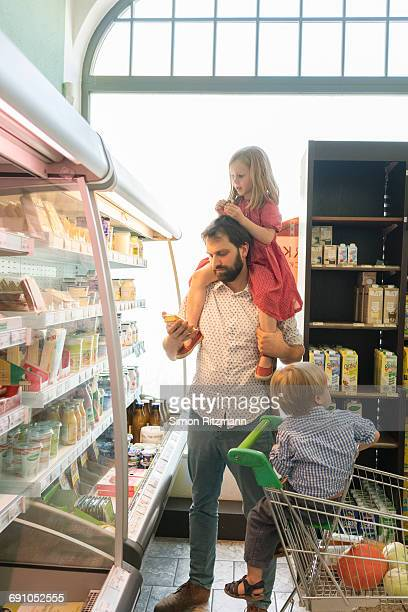 Modern father with two children in grocery store