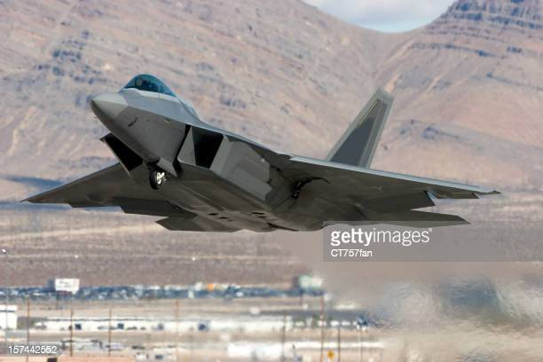 Modern fighter jet flying over mountainous region