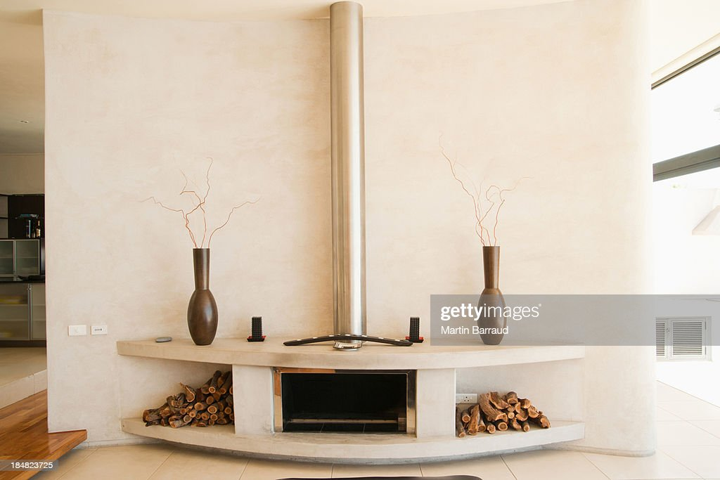 Modern fireplace with wood piles on each side : Stock Photo