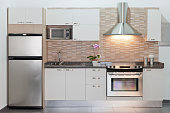Small or compact modern kitchen with appliances. Contemporary style. Sparse design. White cabinets. Example of design for small architectural spaces. Front view, horizontal composition. Kitchen backgr