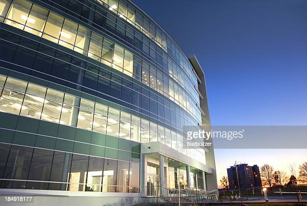 Modern glass office building at sunset