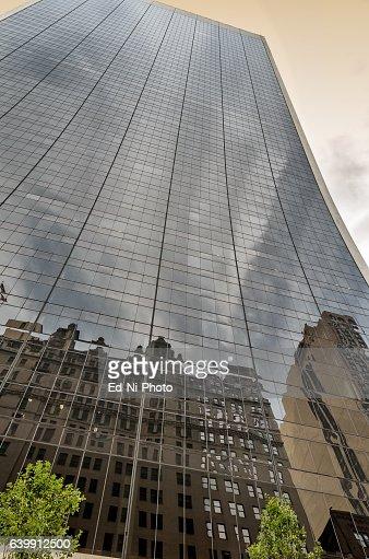 Modern glass skyscraper reflects nearby buildings : Foto stock