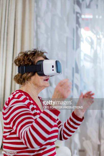 modern grandmother - 90 years old -  is using VR glasses the  first time in her flat