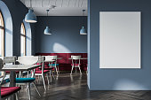 Modern gray cafe interior with a wooden floor, and square tables with blue chairs near them. Soft red sofas along the walls. A poster 3d rendering mock up