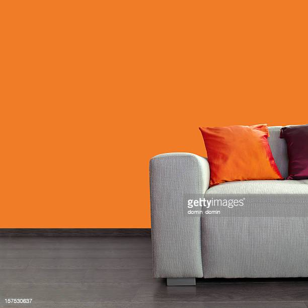 Modern gray sofa and colorful pillows against orange wall