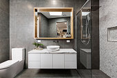 Modern grey designer bathroom with herringbone shower tiling