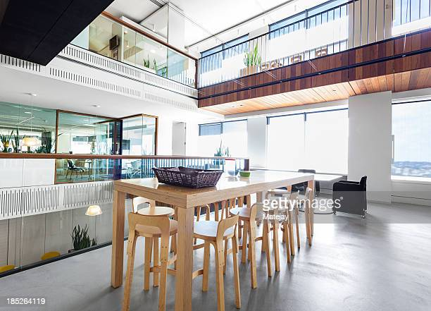 Modern, high wooden table in a large office space
