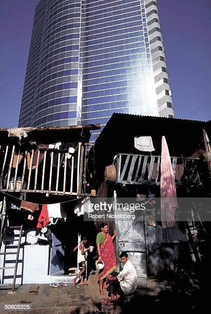 Modern highrise bldg looming behind slum residents outside laundry lineshung shacks