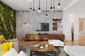 Modern hipster apartment interior. Open space loft, living room with large white sofa, vintage decorative carpet, coffee table with coffee, seat. Large pendant light. large windows with sunlight, gree