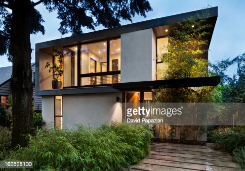Modern home exterior lit at twilight : Stock Photo