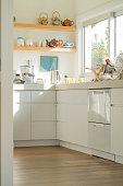 Modern home kitchen in white with wooden floor