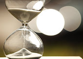 Modern Hourglass -- sand trickling through the bulbs of a crystal sand glass. every second counts. symbol of time. countdown.