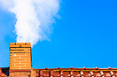 Modern house roof with chimney smoke, air pollution and smog in winter, ecological issues