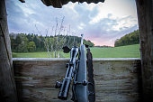 Modern black hunting rifle with a scope in hunting hide and a beatiful view on sunset and fields and forest