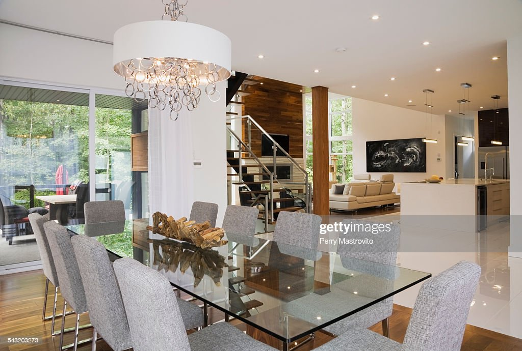 Modern Interior Design Luxury Open Plan Dining Room With Glass Dining Table  And Grey Upholstered Dining Chairs Stock Photo | Getty Images
