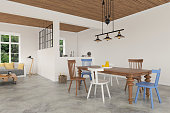 White apartment interior showing comfortable living room sofa on the left, and a wooden dining table with colorful chairs. There are windows showing green nature scenery. Concrete polished floor with