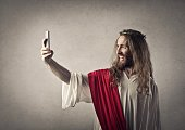 Smiling Jesus Christ is taking a selfie with his phone