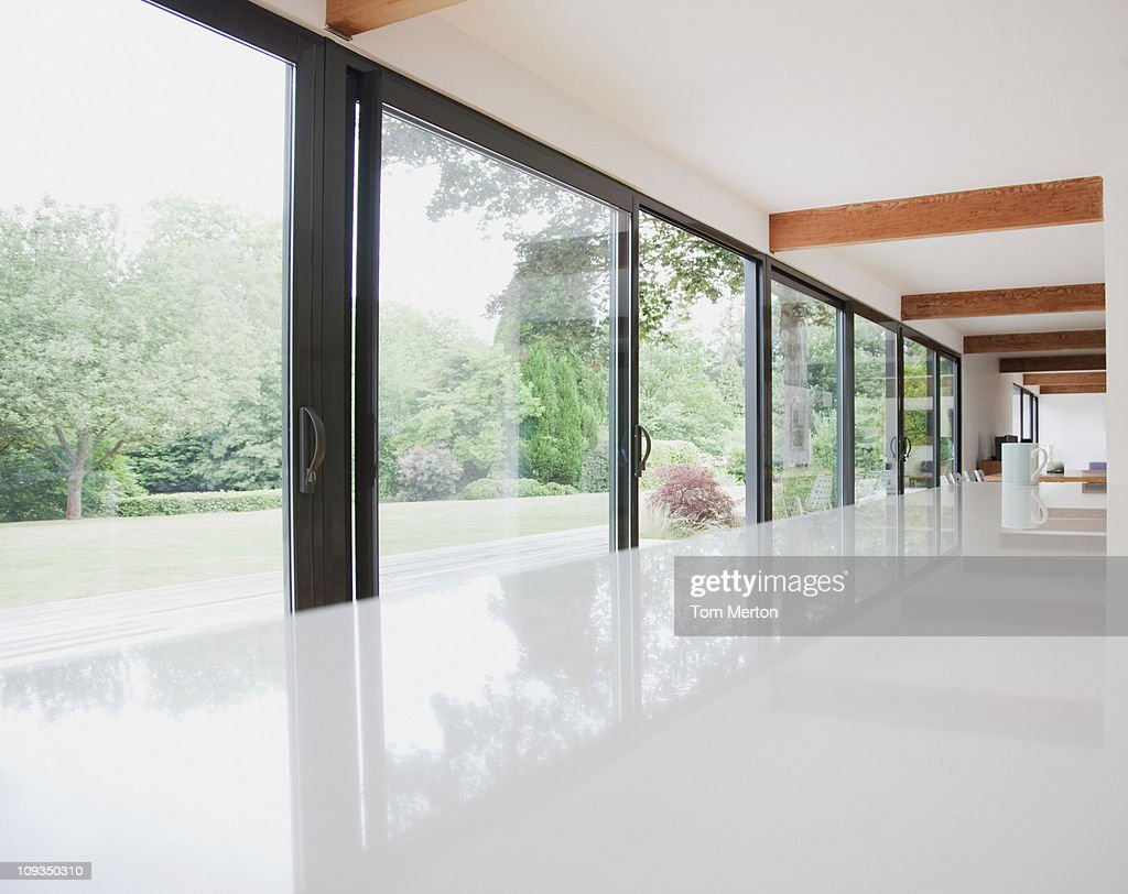 Modern kitchen and glass walls to backyard : Stock Photo