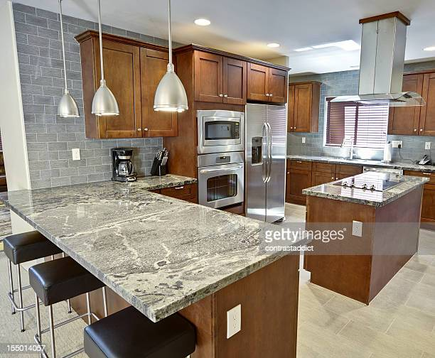 Modern kitchen interior with dark units and marble counters