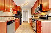 Modern kitchen interior. Cherry wooden cabinets with marble counter tops blends with steel appliances