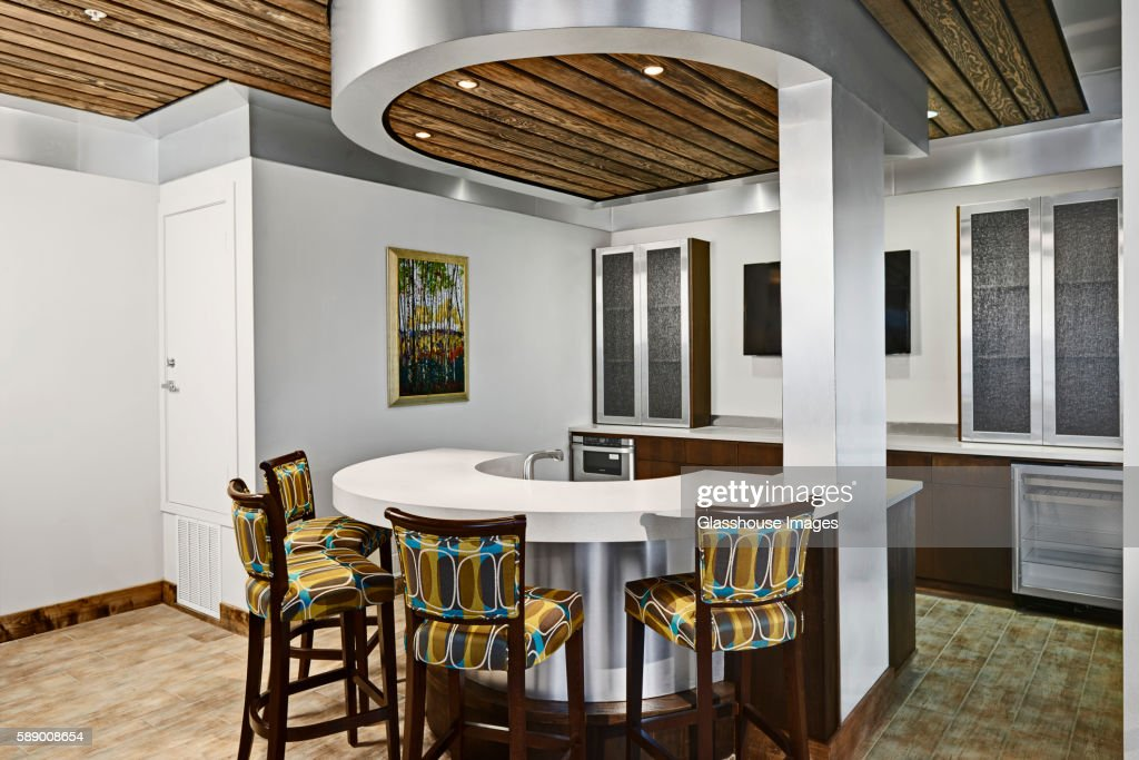 Modern Kitchen With Circular Counter and Colorful Counter Stools