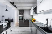 Modern black and white kitchen with rustic ceiling and brick effect tiles