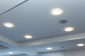 Modern layered ceiling with embedded lights and stretched ceiling inlay, lights on.