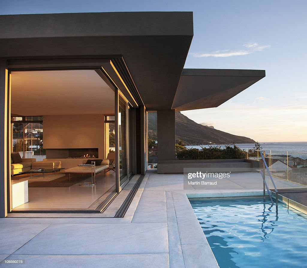 Modern living room and patio next to swimming pool : Foto de stock