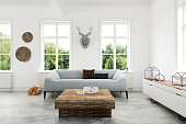 White modern living room interior with a direct view at comfortable gray sofa. There are windows showing green nature scenery. Concrete polished floor with wooden coffee table. Lots of decorative deta
