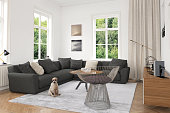 White modern living room interior with comfortable gray sofa with pillows. Coffee table with decoration. There are windows showing green nature scenery. Parquet wooden floor with gray carpet. Lots of