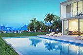 Modern villa exterior with pool and beautiful view at dawn.