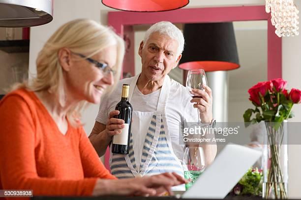 Couple senior, préparer la nourriture moderne et travaillant sur un ordinateur portable