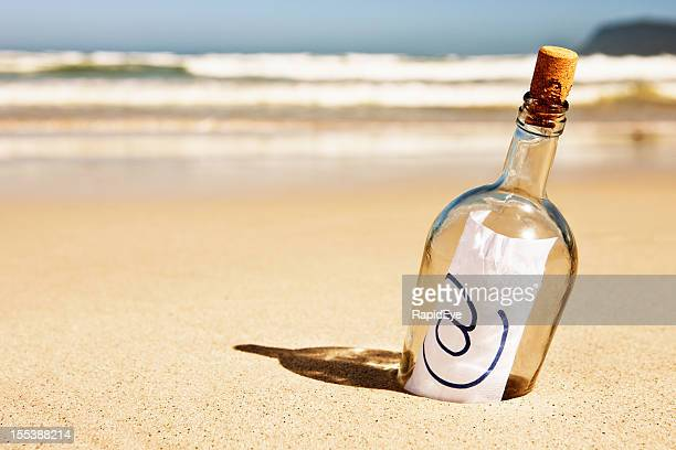 "Modern message in a bottle on beach says simply ""@"""