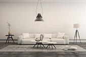 Horizontal frame showing a penthouse loft living room, with white sofa, concrete floor with a rug, decorative tables, a lamp, industrial chandelier and decoration.