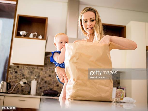 Modern Mom Unpacking Groceries with Infant Girl In Arms