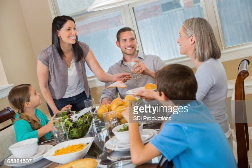 Modern mother serving dinner to her three generation family