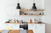 Modern new light interior of kitchen with white furniture and dining table
