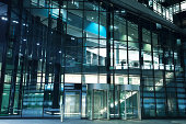 Modern Office Building Entrance with Revolving Doors at Night